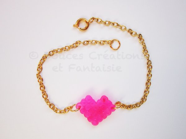 Bracelet doré et coeur fuchsia