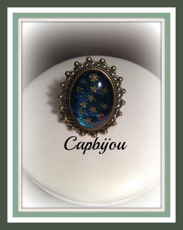 bague bronze orn� d'un cabochon �toil� sur fond turquoise aux reflets iris�s