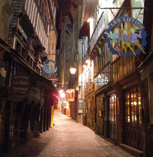 le mont st michel (l)  Au 15ème siècle, la construction du système défensif de l'abbaye étant achevé, la protection de la ville fut envisagée. Trois portes défendent l'entrée de la ville. La première, accolée au corps de garde des bourgeois, est connue sous le nom de porte de l'Avancée. Ses défenses sont sommaires. La seconde porte, défendue par une redoute et une demi-lune, s'appelle la porte du Boulevard. La porte la plus défensive est sans conteste celle du Roi, protégée par les tours de l'Arcade et de du Roi, elle pouvait difficilement être franchi car un pont-levis et une herse en barrait le passage. Passé le seuil de la porte du Roi, le visiteur se trouve sous un passage voûté qui faisait office de corps de garde. Les pièces situées au dessus de ce passage abritent aujourd'hui la mairie du Mont Saint-Michel. Vous avez maintenant devant vous la Grande Rue. Rue unique du Mont, elle tourne autour du rocher pour mener le visiteur au pied du grand degré extérieur. L'été, l'ascension de la rue se fait, entre les boutiques de marchands de souvenirs, au milieu d'une foule compacte et cosmopolite. Il devient dans ces conditions très difficile d'apprécier les constructions bordant cette rue et mieux vaut la quitter sans regrets. Alors, emprunter les venelles et autres passages désertés par les touriste avides de bimbeloteries permet de se replonger dans une époque où la beauté des choses nous fait oublier les vicissitudes de la vie actuelle.  (l)