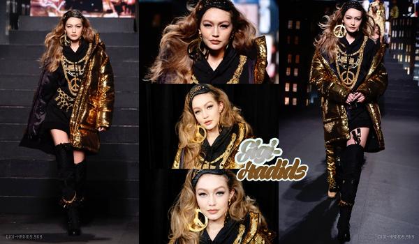 24/10/2018 •  Gigi Hadid faisait le final du Fashion Show à New York. Elle portait la collection de Moschino x H&M.  Je trouve que la tenue fais très bling-bling haha. C'est voyant mais j'aime l'association du noir et or. Ça lui va bien même si je trouve la tenue chargé. La mise en beauté est réussis par contre.BOF.  -