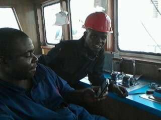le pilote et moi a la cabine d'un bateau .étant ivoirien, pourquoi ne pas fait connaissance avec un Nigérian meme si il était a abidjan pour une réparation.