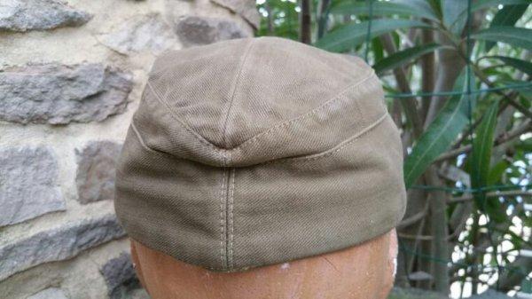 """Casquette 43 Coloniale WH.Feldmütze tropicale (1940/1943). La Feldmütze accompagnant la nouvelle tenue tropicale de 1940 s'inspire de la casquette de montagne. Mais elle est taillée dans la même toile verte olive que l'ensemble de l'uniforme. L' emblème national particulier aux coiffures tropicale est tissé en fil gris-bleu sur un fond fauve. Le """" V """" renversé en soutache à la couleur d'arme disparaît en 1942, comme sur les autres Feldmütze. Aucune  coiffure spécifique n'est prévue pour les officiers."""