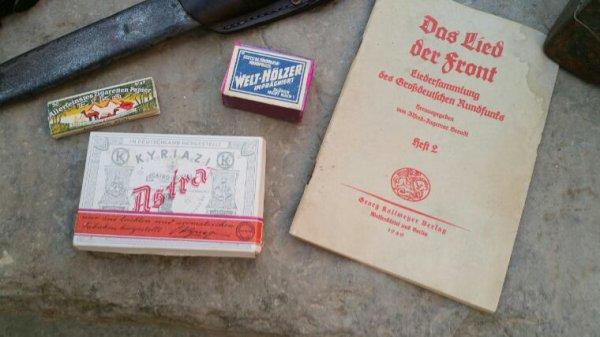 Carnet de chant Allemand de 1940, feuilles de cigarettes, boîte d'allumettes et paquet de cigarettes.