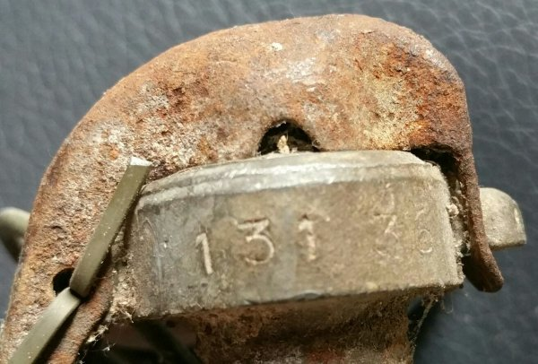 Grenade OF1 mle 1915 appelée également pétard d'assaut. Cet grenade pèse 250g dont 150g de cheddite en 1915, puis de 120g de schneirite et 105g de NTMX, et est livrée aux armées, non amorcées, par caisses de 200. Le mle d'exercice est peint en rouge ainsi que lesté avec du sable et du gravier.