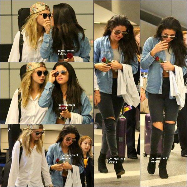 24/07/14 - Selena arrivant à l'aéroport de LAX à L.A avec Cara Delevingne et une rose à la main.