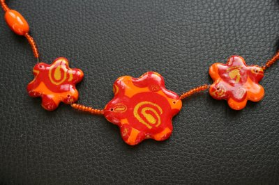 Collier fleurs en fimo avec des spirales orange et jaune