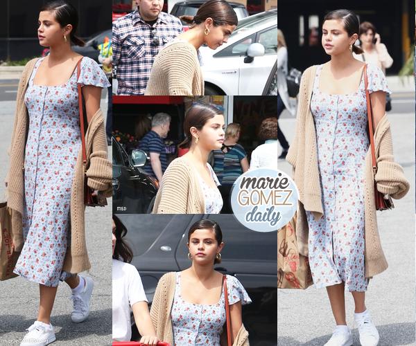 • 01/04/2018 : Flashback de Selena qui quittait le supermarché Trader Joe à Los Angeles.  Mon avis : Sa robe longue lui va assez bien je dois dire. C'est simple et frais pour cet été avec son gros gilet beige. La mise en beauté est simple, j'aime !