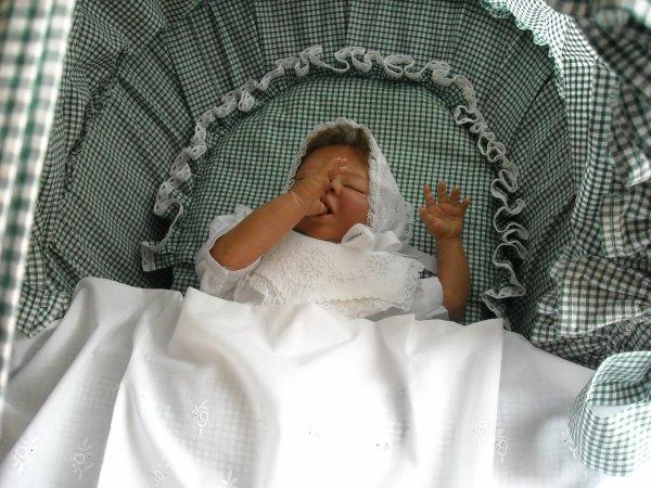 Sophie essaie de trouver son sommeil en suçant son pouce. Elle est couchée dans le moïse que j'ai réalisé pour la naissance de mon premier petit-enfant.