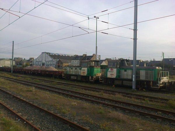 Deux locotracteurs Y8000 attelés à un train de ballast en gare de Lamballe