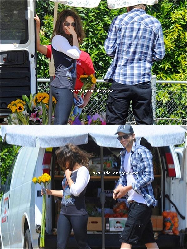 """. 20 avril 2012 : Ash' a été vu avec son """"amie"""" Mila Kunis allant dans un stand en Californie. ."""