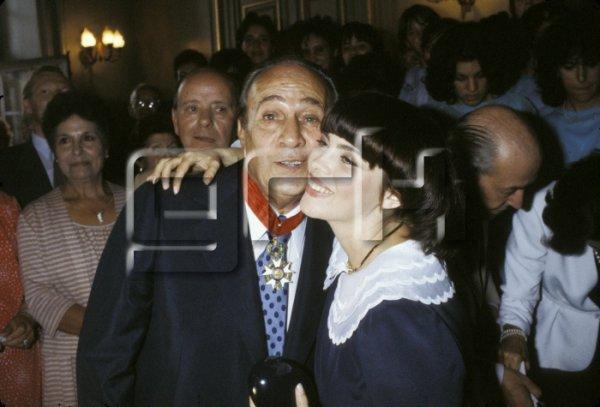 Le 14 septembre 1982, Mireille MATHIEU félicite Tino ROSSI qui vient de recevoir la cravate de Commandeur dans l'Ordre de la Légion d'Honneur, des mains du Ministre de l'Intérieur Gaston Defferre
