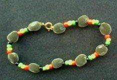 un bracelet fait de graines de zanzibars et de perles rouge jaune vert noir