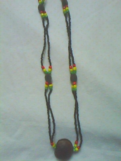 c'est un collier rouge jaune vert noir avec des graines de zanzibar et un oeil de boeuf en pendentif