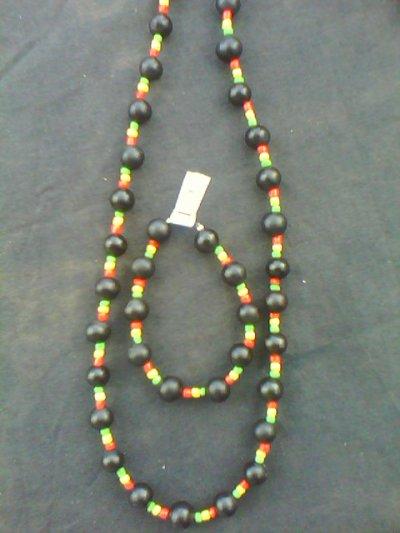 un collier et son bracelet fait de graines de savonnette et de perles de rocaille rouges jaunes et vertes