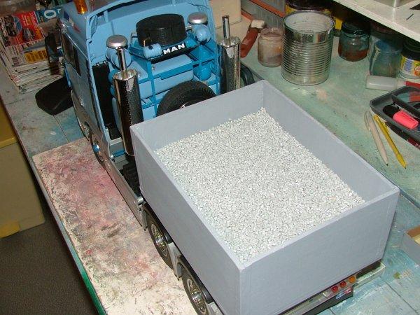 chargement de la caisse une couche de petits cailloux un morceau de feraille et des granuler de plastiques poids 2 k 900