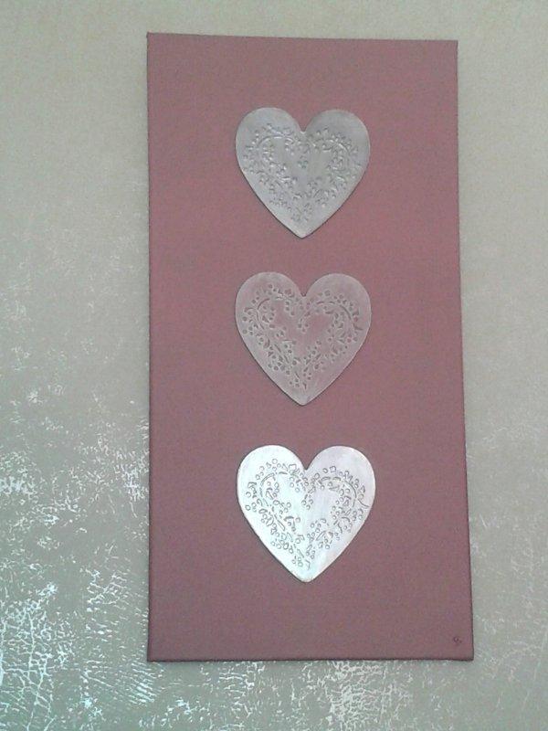Toile c½ur, fond satinelle poudre, 3 c½urs collés (patapoch c½ur en relief). Le coeur du centre est couleur poudre avec un décoglacis aluminium et les 2 autres en aluminium, vitrificateur pour protéger le tout.