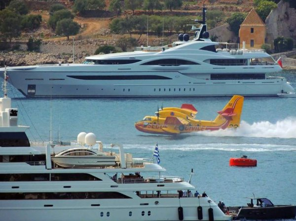 Canadair fighting a forest fire alongside luxury yachts