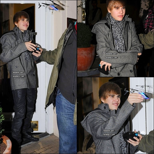 Justin, quittant hier , un restaurant au c½ur de Londres avec une fausse moustache et jouant avec un avion.