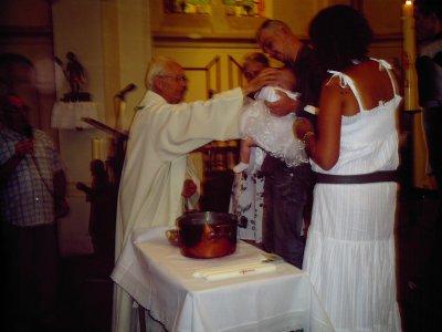 le pretre fait le signe de croir sur son fron