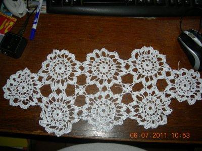 voici un napperon fait en fil blanc brillant