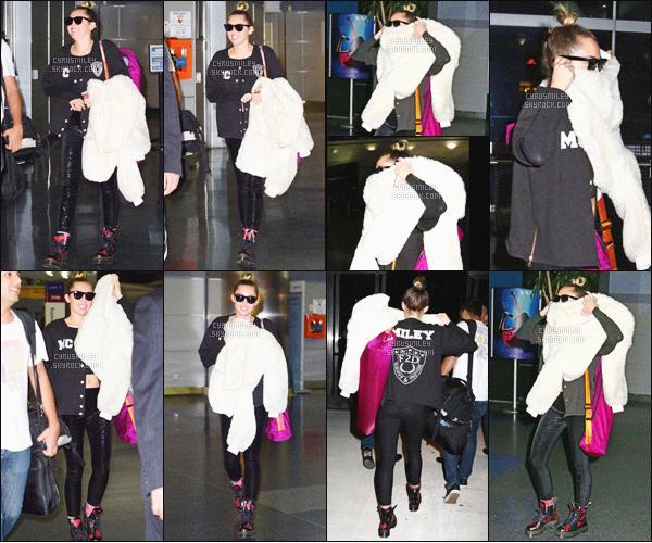 """. ♦♦ 28 Février 2016 : La jolie Miley Cyrus à été photographié toute souriante arrivant à l'aéroport JFK de New-York. • Niveau look : Miss Cyrus était vétu d'un pull avec inscrit à l'arrière """"Miley"""", d'un leegins ainsi qu'une paire de Doc Martens !."""