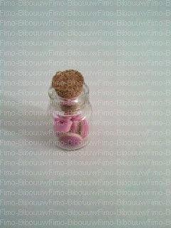 Fiole avec marshmallow tortillé rose et blanc et donut's rose et violet