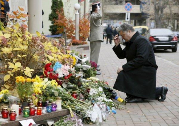 Le président ukrainien Petro Poroshenko agenouillé devant l'ambassade de France en hommage aux victimes civiles des attentats du 13 novembre, à Kiev, en Ukraine, le 14 novembre 2015