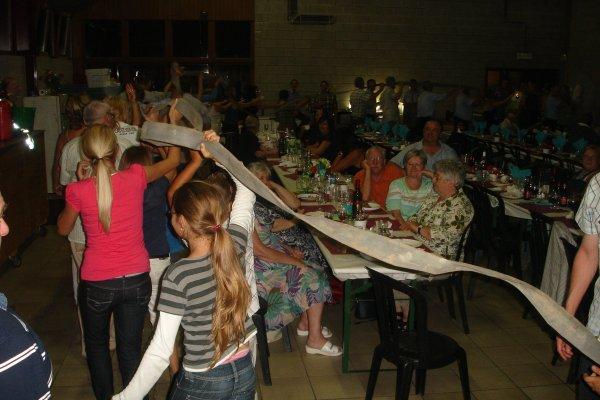 UNE RONDE DE 132 PERSONNES AVEC UN TUYAU LANCE D'INCENDIE POUR GUIDE DANS TOUTE LA SALLE