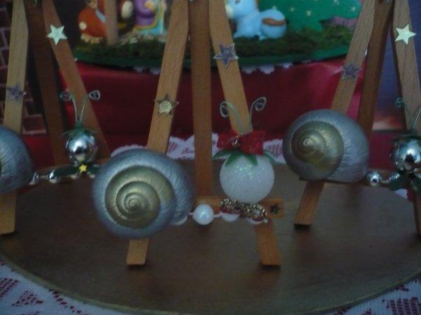 réalisé avec une coquille d' escargot, petites perles,et une petite boule de noel pour la téte