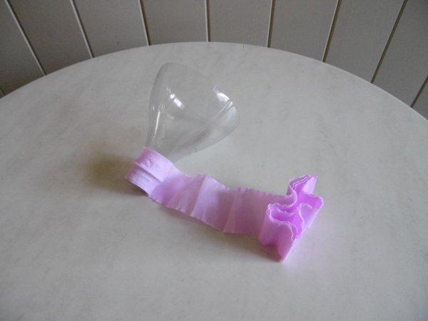 Une coupelle  avec une bouteille en plastique .