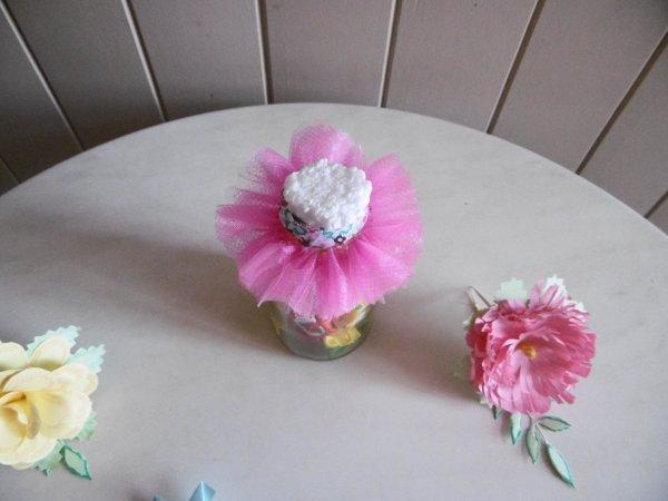 Centre de table avec des bonbons                                  décoré de fleurs et de robes en papier .