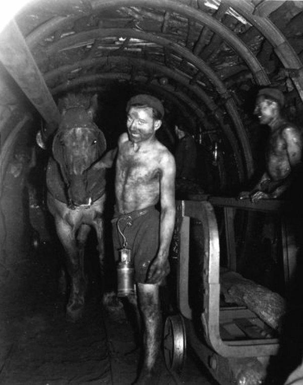 une ançiènne photo dans une galerie un mineur tirer du charbon avec un wagonner dans1945 les années 1945