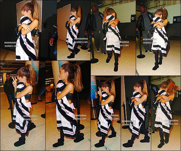 ' 03/12/2014 : Ariana Grande a été photographiée, arrivant à l'aéroport de « L.A.X » situé à Los Angeles.  Face aux photographes, elle n'a pas pu s'empêcher de se cacher derrière son espèce couverture de la marque Victoria Secret. Elle semblait fatiguée. '