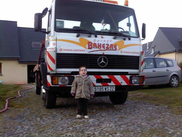 mon petit choux de 3 ans , devant le camion a son papa.
