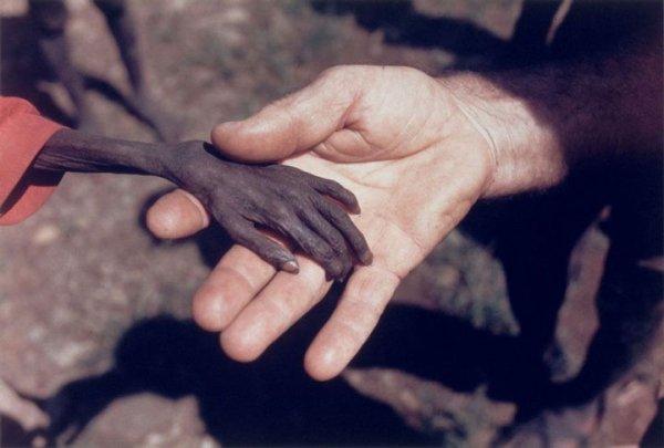 Un petit garçon affamé donne la main à un missionnaire