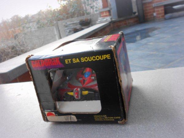 """Soucoupe Goldorak Made In France Window Box. L'essentiel..  Ce que j'espérais, c'était placer quelques pièces rares dans ma collection..  C'est avec la soucoupe """"sous sachet"""" que j'ai compris que je m'inscrivais dans la durée avec ma passion.  Avec quelques pièces moins facile à trouver, on est pas mal, mais on devient intéressant quand on arrive à 500..  Je crois que le jouet est une collection de plaisir et je ne pense pas qu'on puisse donner du plaisir sans le partager avec les autres.  Il arrive un moment ou le jouet rend beau dans une vitrine.  Avec les années, je me demande si un collectionneur n'a pas tout dit avec quelques pièces rares à sons actif, je pense..  Finalement, avec le temps, on tourne en rond dans nos recherches mais un jour ou l'autre même si on est content, il nous manque un jouet """"le Graal"""", pour ma part, celui dans une boite fenêtre que je voyais passé mais qui finalement disparaissait ailleurs à jamais.  Je ne passe jamais devant une vitrine décorée, un jouet en bois, une collection chez un ami, un vieux disque, sans me dire, C'est peut-être le prochain.. Il l'est.  Mais aujourd'hui, j'ai envie de revenir à l'essentiel, merci Stephan🥰  Soucoupe Mattel Goldorak Made In France """"Window Box"""" 1981, 82"""