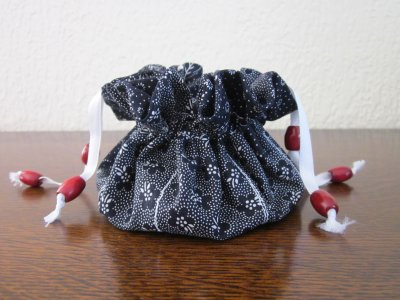 Pochette à bijoux comportant huit petits compartiments latéraux et un central.