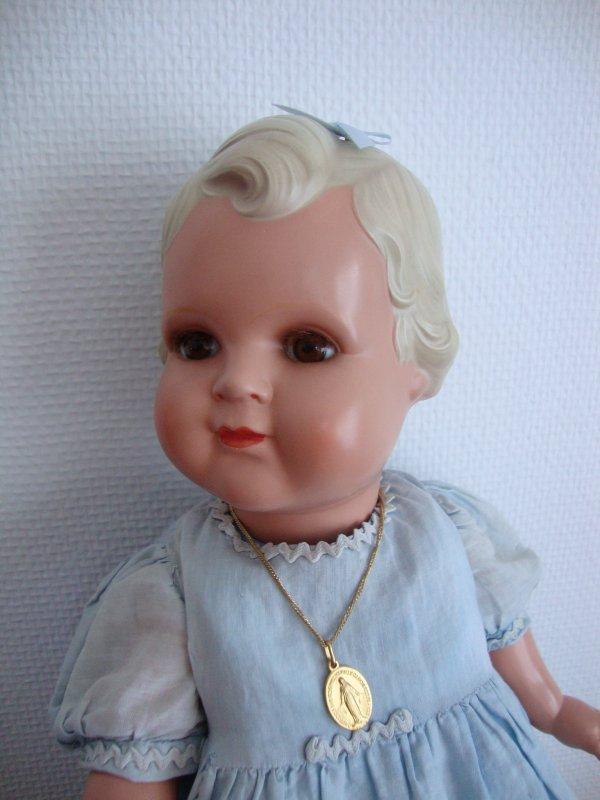 poupée allemande de marque minerva  sur un  dessus de landau ou berceau finement travaillé en soie .