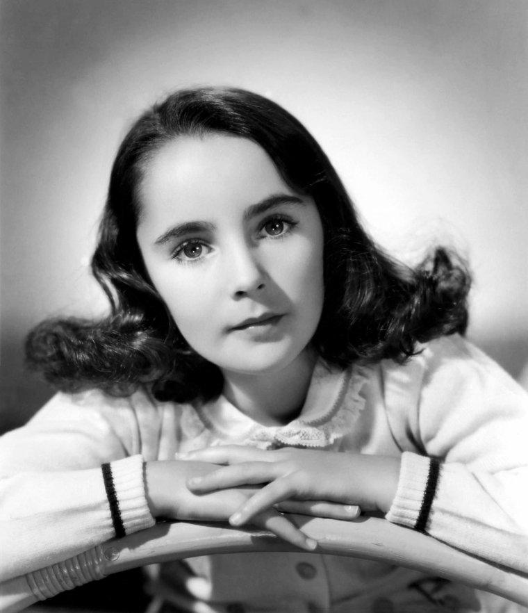 BEAUTIFUL CHILD / Elizabeth TAYLOR naît le 27 février 1932 à Hampstead, situé en Angleterre dans la banlieue cossue de Londres, avec la nationalité britannique, de parents tous deux américains et originaires de Kansas City (Missouri). Elle est la seconde enfant de l'actrice Sara Viola WARMBRODT (de son nom de scène Sara SOTHERN, 1895–1994) et de Francis TAYLOR (1897–1968), propriétaire d'une galerie d'art. Elle grandit au 8 Wildwood Road d'Hampstead Garden Suburb, auprès de ses parents et de son frère aîné Howard TAYLOR (né en 1929). Ses deux prénoms, Elizabeth et Rosemond lui ont été donnés en l'honneur de sa grand-mère paternelle Elizabeth Mary (Rosemond). Le colonel Victor CAZALET, un des meilleurs amis de la famille, a beaucoup d'influence sur cette dernière. Riche et bien introduit, membre du Parlement et proche de Winston CHURCHILL, il est un passionné d'art et de théâtre. Il persuade les TAYLOR de s'établir définitivement au Royaume-Uni. Adepte de Science chrétienne, ses liens avec la famille sont également d'ordre religieux. Il devient le parrain d'Elizabeth et entraîne la famille sur le chemin de sa propre obédience. Le biographe Alexander WALKER suggère qu'il « est probable que la conversion d'Elizabeth à la religion juive, et son long engagement à la cause d'Israël, a pour origine la vision sympathique qu'elle en a eu chez elle au cours de ces années formatrices. ». WALTER note que CAZALET était un propagandiste actif pour un État hébreu et sa mère a milité activement au sein de groupements caritatifs avec des collecteurs de fonds en faveur du sionisme. Elle se souvient de l'influence de CAZALET sur sa fille en ces termes: « Victor s'assit sur le lit et prit Elizabeth dans ses bras tout en lui parlant de Dieu. Ses grands yeux sombres scrutaient son visage, s'imprégnant de chaque parole, croyant et comprenant [ce qu'il lui disait] p. 14 ». Peu avant le début de la Deuxième Guerre mondiale, fuyant les hostilités, les parents d'Elizabeth décident de rentrer 