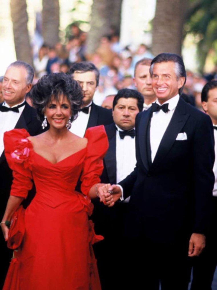"""CANNES 1987 / En 1987, tout le monde se souvient de sa robe rouge incendiaire lors de sa montée des marches à Cannes. Une vraie robe de princesse hollywoodienne, au décolleté drapé resserré à la taille. Le plus: les maxi-manches ballons, sans oublier les bijoux d'oreilles... Elle est accompagnée de son amant du moment, George HAMILTON / C. David HEYMANN, dans son livre """"Liz : La biographie non autorisée d'Elizabeth TAYLOR"""", dresse la liste des amants de la belle actrice, grande séductrice de l'écran dotée d'une vitalité extraordinaire (en témoigne sa résistance à ses problèmes de santé et à ses abus divers). Outre ses amitiés amoureuses avec les plus célèbres homosexuels d'Hollywood (Montgomery CLIFT, Rock HUDSON…) et ses liaisons déjà citées avec les réalisateurs Stanley DONEN et Richard BROOKS et avec l'acteur George HAMILTON, le biographe détaille (de façon parfois choquante) les passades de Liz, avec les acteurs Peter LAWFORD, Victor MATURE, et le chanteur et acteur Frank SINATRA parmi les plus connus de ses amants."""