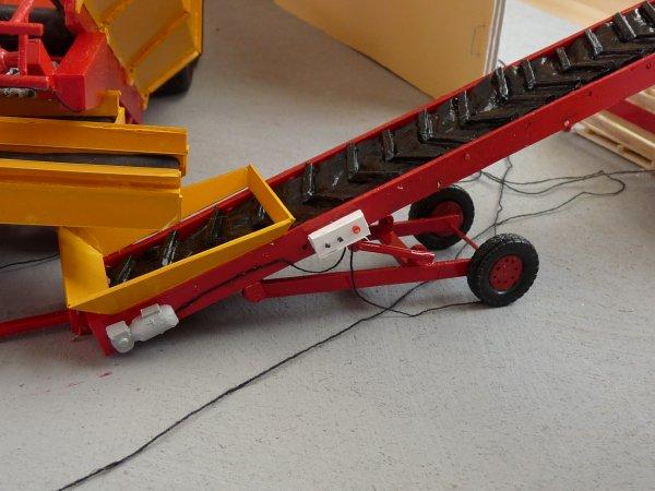 Ensemble déterreur, chargeur de caisses et tapis roulant sur le diorama devant le hangar