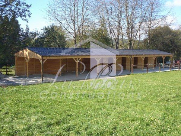 Construction de 5 boxes chevaux accolés à un abri pour le foin, paille... et d'un abri pour remorque, le tout avec un auvent de 2m