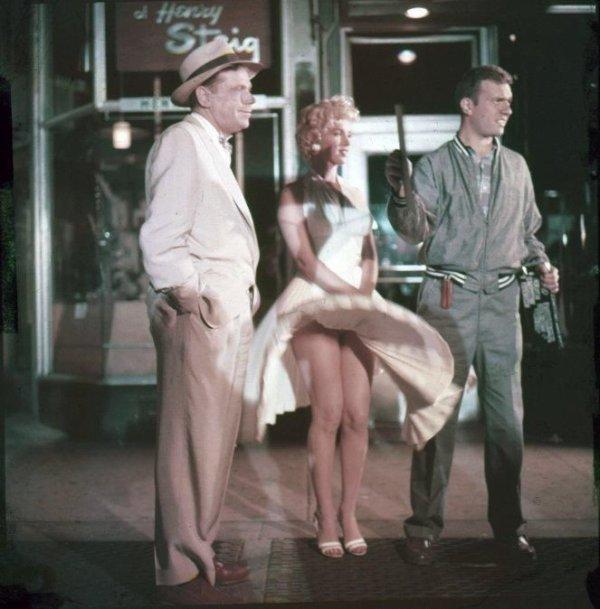 """Scène mythique, où la robe de Marilyn se soulève lors du passage d'une rame de métro, à New-York, 1955, dans le film """"7 ans de réflexion""""... Richard Sherman, un publiciste, vient de déposer à la gare sa femme et ses enfants. Il prévoit de rester seul pour les vacances d'été dans son appartement new-yorkais... film de Billy WILDER... On la voit ici aux côtés de son partenaire, Tom EWELL. (diverses photos du film)"""