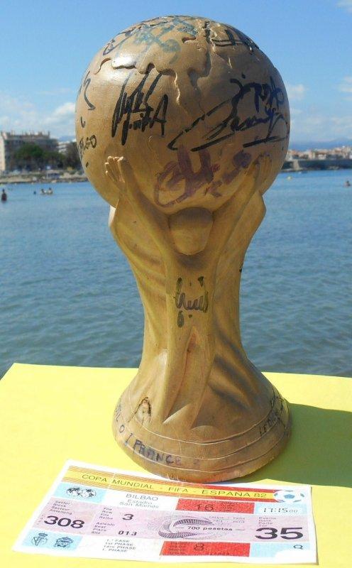 """-- mon """""""" PATRIMOINE  -- ....ma Coupe du Monde en bois , signée par : 13 CHAMPIONS du Monde de 1998 ..... et mon 1ér billet du : 16 juin 1982 pour FR/ ANGLETERRE à Bilbao .....PHOto avec ma femme Eliette ,  prise de la plage de la SALIS , avec en arriére plan ... les remparts d'ANTIBES ...."""