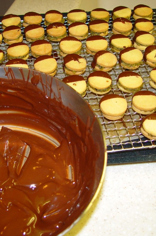 Fait avec du chocolat, de la pâte sablée et remplie de pistaches.   Hergestellt mit Schokolade, aus Mürbeteig und mit Pistazien gefüllt…