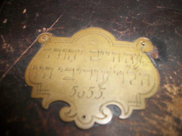 Plaque en cuivre acrochée sur la couverture du dite livre