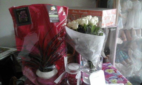Voici un avant goût de mes cadeaux. Plante, gros bouquet de roses et une surprenante bougie qui une fois allumée dévoile des boucles d oreilles. .......a suivre