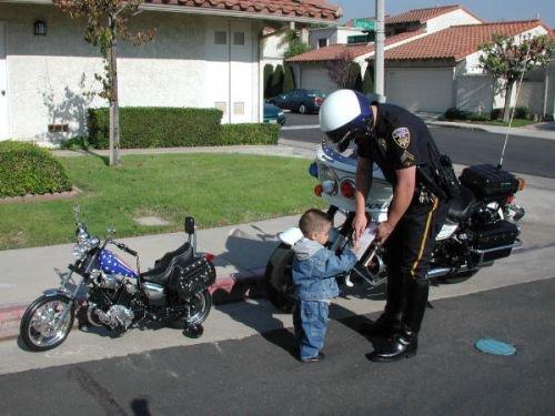 Il est interdit d'enfreindre la loi, même si vous avez 4 ans ! Cet enfant, qui ne doit pas faire plus d'un mètre de hauteur, se fait controler par la police pour avoir grillé un feu rouge, à bord de sa super moto. Quel motard ! Ceci est à prendre très au sérieux, bien entendu…