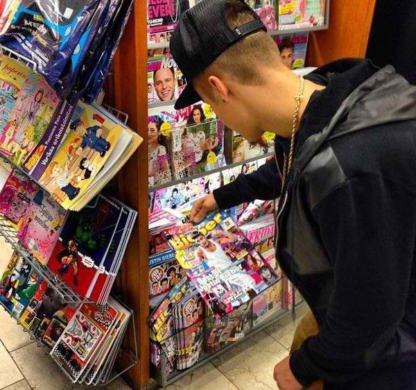 Justin qui regarde la couverture d'un magazine où il fait la une