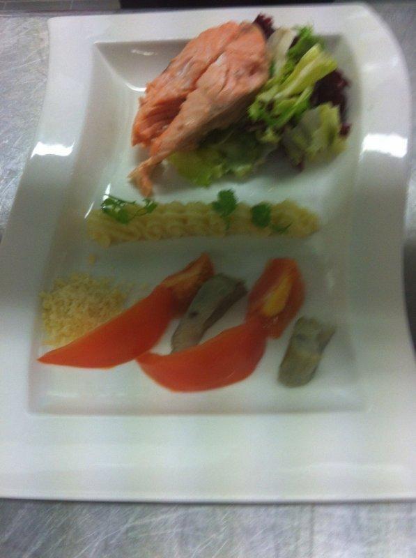 Darne de saumon sur son dôme de salade avec sa mayonnaise c'est tomate et c'est c½ur d'artichaut et sont parmesane râpe.